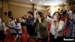 Members of the main opposition Minjoo Party of Korea react as they watch a news report on results of exit polls in Seoul, South Korea, April 13, 2016.