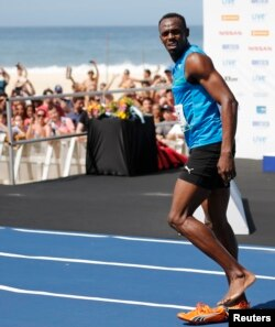 """Jamaican Olympic gold medallist Usain Bolt looks on after winning the """"Mano a Mano"""" men's 100 metres challenge on Copacabana beach in Rio de Janeiro on Aug. 17, 2014."""
