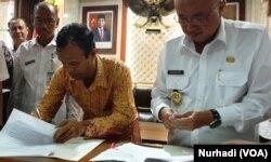 Pendeta Sitorus dan Suharsono menandatangani kesepatan di luar pengadilan terkait ijin bagi GPdI Immanuel di Kabupaten Bantul, DIY. (Foto:VOA/ Nurhadi)