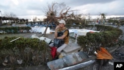 A man sits in the debris with an uprooted tree seen in background, after powerful typhoon Haiyan slammed into Tacloban, central Philippines on Saturday, Nov. 9, 2013.