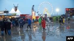 Visitors to the music festival Rock am Ring are seen wading through mud after a heavy downpour in the west German city of Mendig, June 3, 2016. Organizers canceled the final day of the three-day event after lightning strikes injured at least 72 fans.