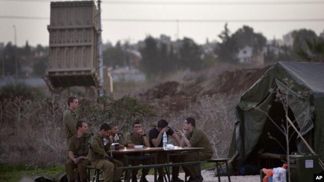 Binh sĩ Israel ngồi cạnh hệ thống phòng thủ phi đạn 'Vòm Sắt' ở Tel Aviv, ngày 17/11/2012.