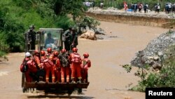 Rescue workers are transported into an earthquake zone on a front loader in Zhaotong, Yunnan province, August 5, 2014.