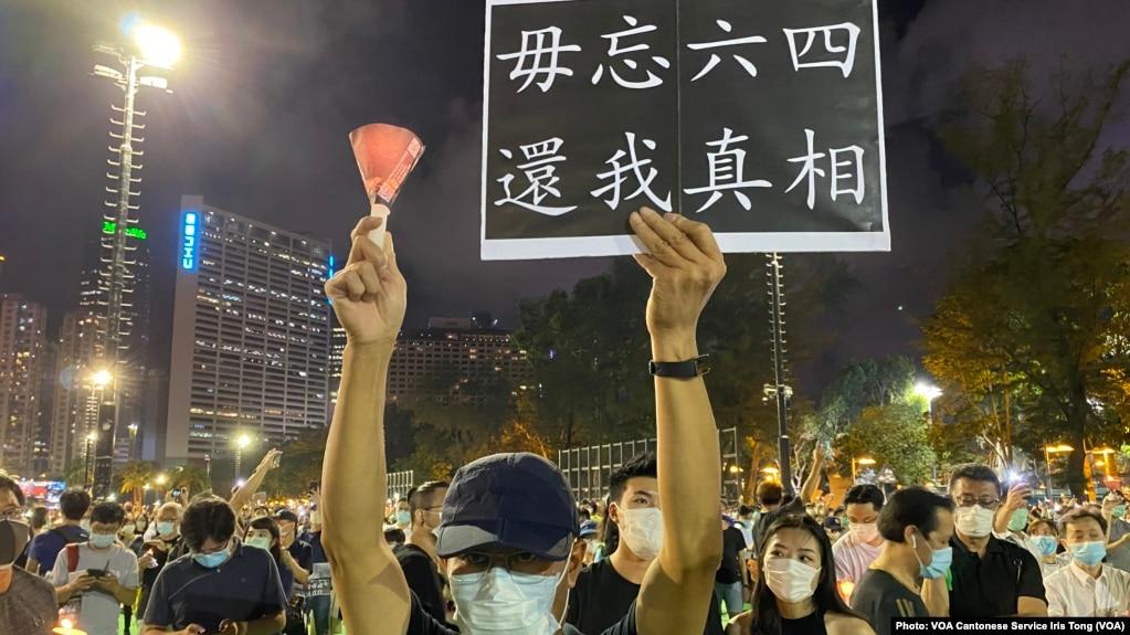 """六四31周年香港人首次进行""""非法""""维园烛光悼念集会,数以万计市民响应,有人高举烛光及标语 (美国之音汤惠芸拍摄)"""