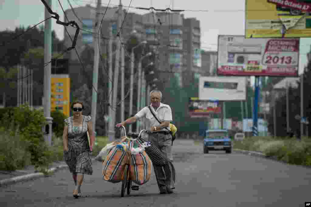 People carry their belongings using a bicycle as they leave Slovyansk, eastern Ukraine, June 9, 2014.