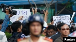 "Police and security personnel film protesters holding placards which read, ""Haiyang 981 oil rig get out of Vietnam (left)"" and ""Take China to the international court"" (right) during an anti-China protest in Vietnam's southern Ho Chi Minh city May 18, 2014."