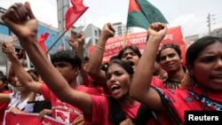 FILE - Garment workers and activists shout slogans during a rally in Dhaka May 1, 2014.