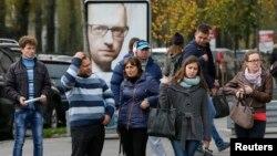 烏克蘭首都基輔民眾10月21日在烏克蘭總理亞采紐克海報前。