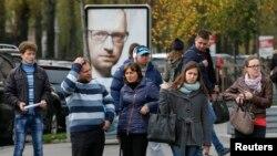 Ukrajinci u Kijevu stoje ispred bilborda sa likom ukrajinskog premijera Arsenija Jacenjuka, 21. oktobra 2014.