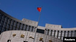 FILE - A Chinese national flag flutters outside the headquarters of the People's Bank of China, the Chinese central bank, in Beijing.