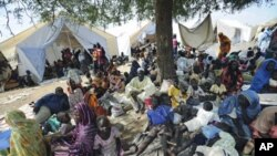 Residents gather outside United Nations Mission in Sudan sector headquarters, where as many as 40,000 people have fled fighting in the region, in Kadugli town, capital city of South Kurdufan State, Sudan, June 2011 file photo
