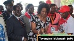UMongameli Robert Mugabe, umkakhe uGrace Mugabe, labanye abaduzane loMugabe basika ikhekhe.
