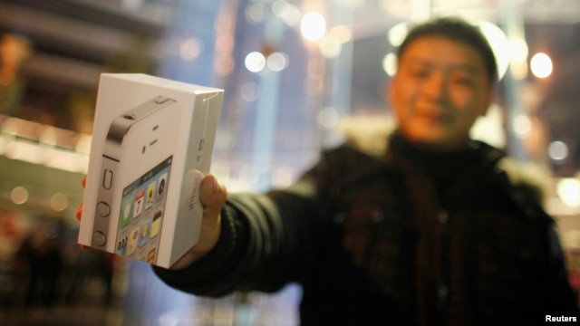 A customer show his new iPhone 4S after making the purchase at Apple's retail store in downtown Shanghai, January 13, 2012.