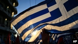 A supporter of the extreme far-right Golden Dawn political party waves a Greek flag during a pre-election rally, in Athens, Sept. 16, 2015.