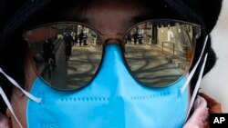 People are reflected on a volunteer's sunglasses outside a closed neighborhood alley following the coronavirus outbreak in Beijing, Sunday, March 1, 2020. (AP Photo/Andy Wong)