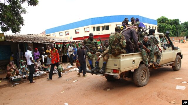 FILE - Militias of the Seleka alliance drive past stalls at the central market in Bangui, Central African Republic, in March, 2013.