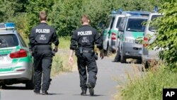 Police officers walk to the crime scene near the river Main, background, where a 17-year-old man from Afghanistan was shot the night before, near Wuerzburg, Germany, Tuesday, July 19, 2016.