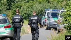 Petugas polisi berjalan ke TKP dekat Sungai Main dimana seorang remaja asal Afghanistan berusia 17 tahun ditembak mati malam sebelumnya. Wuerzburg, Jerman (19/7). (foto: AP Photo/Michael Probst)