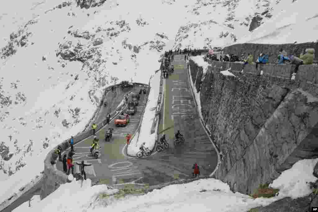 Cyclists pedal along hairpin bends as they climb the Stelvio Pass, 2,757 meters (9,045 ft) above sea level, during the 18th stage of the Giro d'Italia cycling race from Pinzolo to Laghi di Cancano, northern Italy, Thursday, Oct. 22, 2020. (Fabio Ferrari/L