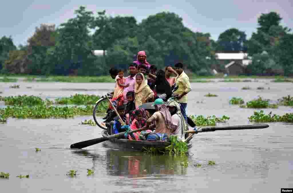 អ្នកភូមិដែលរងគ្រោះដោយសារទឹកជំនន់ជិះទូកទៅរកកន្លែងមានសុវត្ថិភាពនៅក្នុងភូមិមួយនៅក្នុងស្រុក Morigaon រដ្ឋ Assam ប្រទេសឥណ្ឌា។