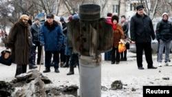 Жители смотрят на остатки хвостовой части ракетного снаряда, разорвавшегося на одной из улиц Краматорска на востоке Украины. 10 февраля 2015 г.