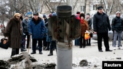 People look at the remains of a rocket shell on a street in the town of Kramatorsk, eastern Ukraine, Feb. 10, 2015. T