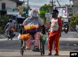Seorang perempuan berkursi roda dan putranya, mengenakan masker dan pelindung plastik di tengah pandemi COVID-19, berjualan jajanan di sepanjang jalan di Pekanbaru, Riau, 20 Juni 2020. (Foto: WAHYUDI/AFP)
