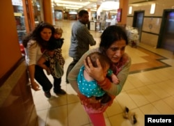 Women carrying children run for safety as armed police hunt gunmen who went on a shooting spree in Westgate shopping center in Nairobi, Sept. 21, 2013.