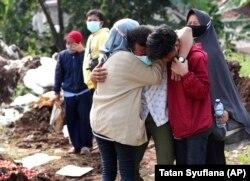Anggota keluarga saat pemakaman kerabatnya di Pemakaman Srengseng Sawah yang diperuntukkan bagi mereka yang meninggal karena COVID-19, di Jakarta, Rabu, 9 Juni 2021. (Foto: AP/Tatan Syuflana)