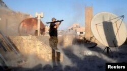 An American volunteer fighter of Syrian Democratic Forces fires an RPG during a battle with Islamic State militants in Raqqa, Syria, Oct. 6, 2017. An American surrendered to US-backed fighters in Syria in mid-September and is being held as an unlawful com