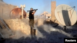 FILE - An American volunteer fighter of Syrian Democratic Forces fires an RPG during a battle with Islamic State militants in Raqqa, Syria, Oct. 6, 2017.