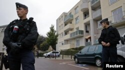 French gendarmes secure a garage entrance, where an anti-terrorist raid was conducted four days ago, in Torcy near Paris, October 10, 2012.