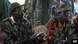 The leader of the Lord's Resistance Army, Joseph Kony , left, and his deputy Vincent Otti sit inside a tent Sunday 12, 2006 at Ri-Kwamba in Southern Sudan