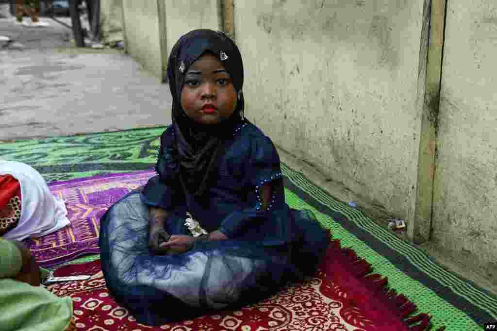 ក្មេងស្រីម្នាក់អង្គុយនៅលើកន្ទេល នៅពេលដែលក្រុមអ្នកបួងសួងបានមកដល់ដើម្បីធ្វើពិធីបួងសួងក្នុងពិធីបុណ្យ Eid-al-Adha នៅទីក្រុង Kara រដ្ឋ Ogun ស្ថិតនៅភាគនិរតីនៃប្រទេសនីហ្សេរីយ៉ា។