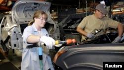 在密西根州一家福特汽车制造厂里,一名女工与男工人一起工作