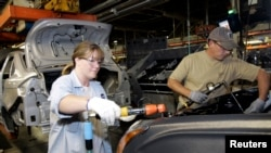 在密西根州一家福特汽车制造厂里,一名女工与男工人一起工作。