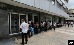 Customers lineup outside of a bank to get cash, in Caracas, Venezuela, Sept. 23, 2017.