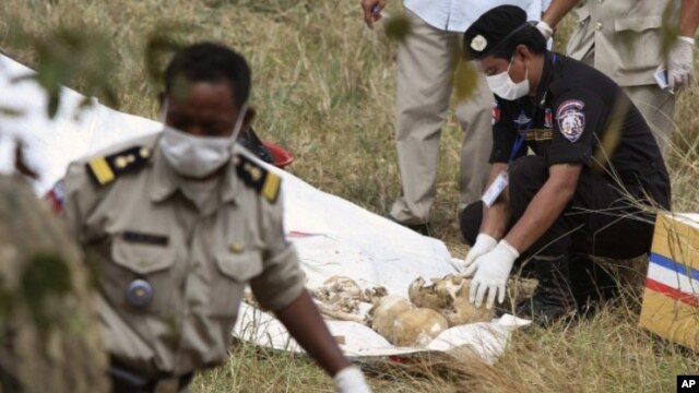 Police officials collect skulls and bones thought to be of Laurent Vallier and his children in Kompong Speu province January 15, 2012.