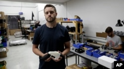 FILE - Cody Wilson, with Defense Distributed, holds a 3D-printed gun called the Liberator at his shop, Aug. 1, 2018, in Austin, Texas.