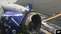 The engine on a Southwest Airlines plane is inspected as it sits on the runway at the Philadelphia International Airport after it made an emergency landing in Philadelphia, April 17, 2018. (Amanda Bourman via AP)