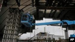 Công nhân xây dựng lắp ráp một vòm thép khổng lồ để che phủ những tàn tích của vụ nổ lò phản ứng tại nhà máy điện hạt nhân Chernobyl, Ukraine, ngày 23 tháng 3 năm 2016.