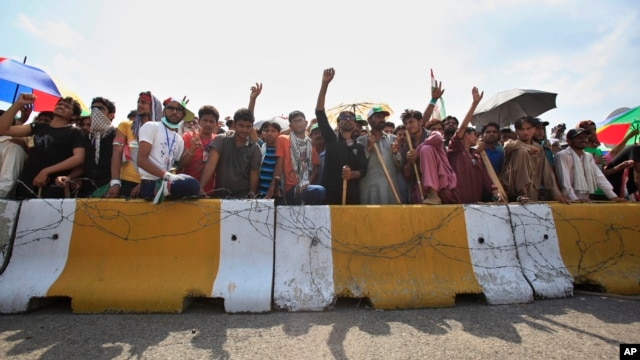 Supporters of anti-government cleric Tahir-ul-Qadri block an entrance of the parliament during a protest at Islamabad's high-security Red Zone in Islamabad, Pakistan, Aug. 20, 2014.