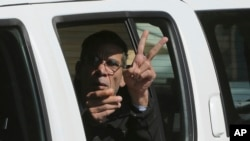 EgyptAir plane hijacking suspect Seif Eddin Mustafa flashes the victory sign as he leaves a EgyptAir plane hijacking suspect Seif Eddin Mustafa flashes the victory sign as he leaves a court in a police car after a remand hearing as authorities investigate him on charges including hijacking, illegal possession of explosives and abduction in the Cypriot coastal town of Larnaca, March 30, 2016.