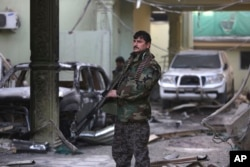 FILE - An Afghan security forces member stands guard at the Spanish Embassy after an attack in Kabul, Afghanistan, Dec. 12, 2015.