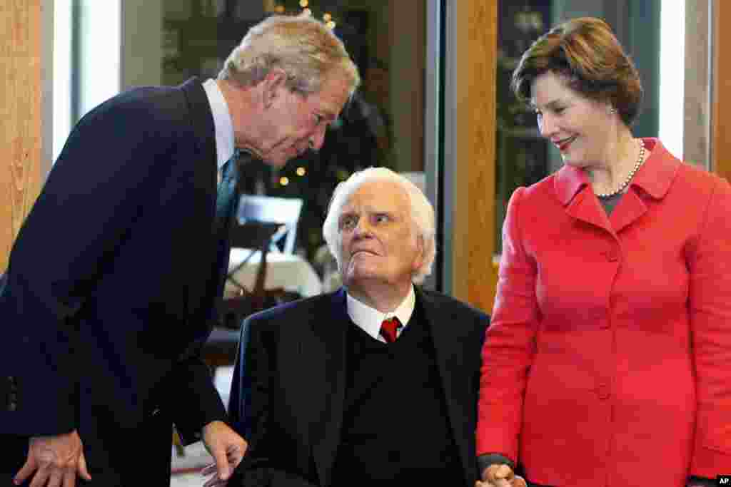 Former President George W. Bush, left, greets evangelist Billy Graham as Laura Bush looks on as they met for a brunch prior to a book signing at the Billy Graham Library in Charlotte, N.C., on Dec. 20, 2010.