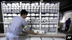 In this Jan. 22, 2016 photo, worker Nguyen Thanh Vuong carries a shelf of potteries, preparing them for the kiln in a factory in Bat Trang village, Hanoi, Vietnam. (AP Photo/Hau Dinh)