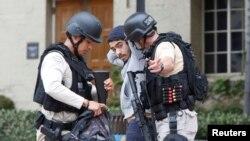 지난 1일 미국 캘리포니아주 UCLA 대학에서 총격 사건이 발생한 가운데, 경찰이 한 학생의 소지품을 검사하고 있다.
