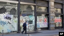 A man walks next to the windows of a closed shop in downtown Milan, Italy, April 12, 2012.