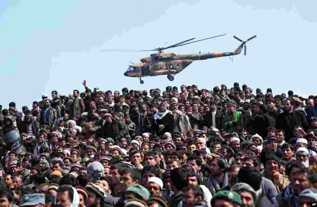 An Afghan National Army (ANA) helicopter flies as Afghan men attend the burial of Vice President Mohammad Qasim Fahim in Kabul.