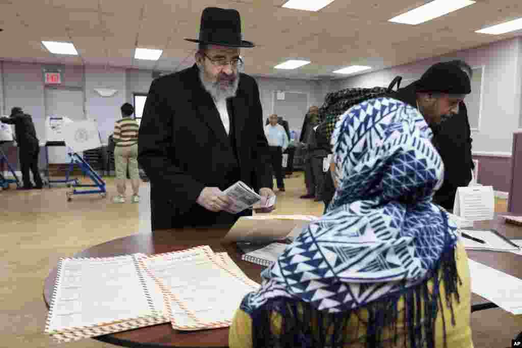 អ្នកបោះឆ្នោត (ខាងឆ្វេង) ផ្ទៀងផ្ទាត់អាសយដ្ឋានរបស់គាត់ជាមួយបុគ្គលិកបោះឆ្នោតមុនពេលបោះឆ្នោត កាលពីថ្ងៃអង្គារ ទី៨ វិច្ឆិកា ២០១៦ នៅក្នុងសហគមន៍ Boro Park ក្នុងទីក្រុង Brooklyn រដ្ឋ New York។ សហគមន៍នេះមានពលរដ្ឋកាន់សាសនា Jewish និងអ៊ីស្លាម។ (រូបភាព៖ AP/ Mark Lennihan)